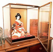 A porcelain Geisha doll in a timber display case