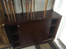 A Ricketts & Thorpe timber credenza with sliding doors revealing two shelves, H 86 x W 122 x D 44cm