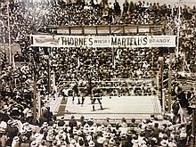 Jack Johnson vs Tommy Burns - an original panorama by Charles Kerry showing the World Championship Battle at Sydney Stadium in progr...