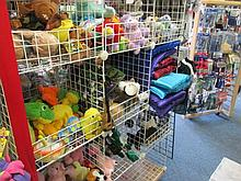Assortment of plush dog toys and satin dog beds.