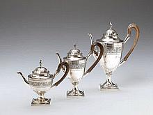 Three Augsburg silver interior gilt pitchers. One large coffee pot, one hot milk jug and one teapot. With carved wooden handles. Marks of Johann Heinrich Busch, 1807 - 10.