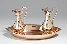 A Parisian silver gilt communion garniture. Comprising wine and water jugs on an oval tray. Marks of Jean-Baptiste Famechon, 1796/97.
