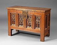 A small gothic cast-iron mounted oak chest with carved decor