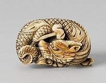 An ivory netsuke of a coiled dragon. Around 1800
