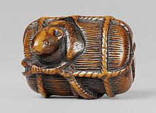 A large boxwood netsuke of a rat in a rice bale. Early 19th century