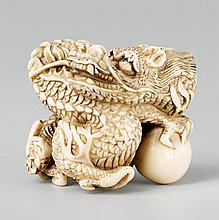 A large ivory netsuke of a coiled dragon. Early 19th century