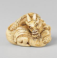 An ivory netsuke of a coiled dragon. Early 19th century