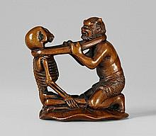A boxwood netsuke of an oni and a skeleton. Late 19th century