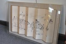 Asian folding panel within a lucite box