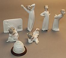Five Lladro white glazed figurines; three children in nightshirts, Girl Stretching, Boy Yawning and Boy Kissing (repaired at neck); ...