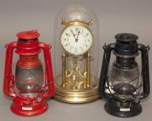 Three pieces; Welby self winding Anniversary clock under glass dome and pair of tin oil lanterns.