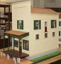 Painted wood dollhouse General Store, two-story with an apartment on a second floor, attached porch on side.