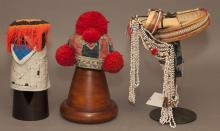 Three Continental Asian headdresses on stands.