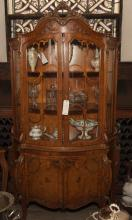French Louis XV design china cupboard with pierced crest above a pair of glazed doors and a pair of cupboard doors