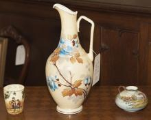 Three assorted pieces of porcelain - large pitcher with floral design, 19th century Royal Doulton cup, and two handled vase
