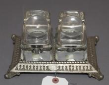 Two-well glass inkwell on metal base, each having magnifying glass lid.