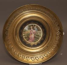 English Regency bone china plate with transfer decoration of a couple in garden scene, in gilt metal frame.
