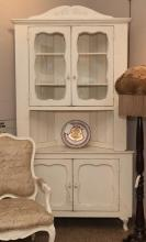 White corner cupboard having a pair of glass doors above an open compartment and a pair of paneled doors