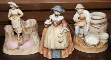 Three continental porcelain bisque groups, pair of figural spill vases with match holders and a figurine of woman