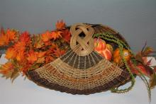 Large finely woven cornucopia with decorative Fall gourds and silk florals