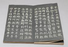 Hand made book with wooden covers unfolds to reveal Chinese characters on handmade paper, presented circa 1920.