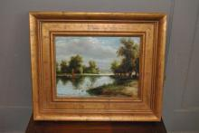 Gilt framed oil on canvas depicting a lake scene with town in background