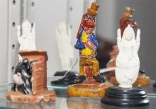 Group of four miniature collectibles, including two Asian carved bone figures and two clay figures