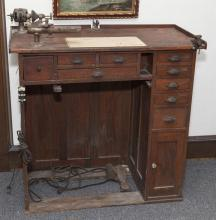 Semi antique oak clock makers desk with tools.