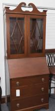 Fall front secretary bookcase with slant front above three drawers on bracket feet