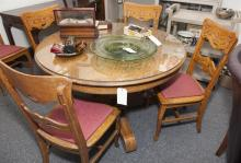 Circular oak dining table with shaped base with four legs