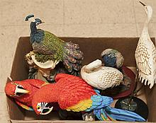 Two decorative peacock figures, two figures of cranes, and a wall plaque depicting two macaws