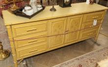 Yellow creme colored dresser with faux bamboo front consisting two cupboard doors flanked by six drawers
