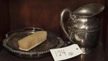 Four pieces of silver; pitcher, serving bowl, handled vessel, and a vanity brush
