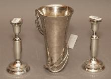 Pair of pewter candlesticks together with a vase, scrolling vine