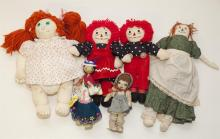 Collection of assorted cloth dolls with embroidered facial features and Cabbage Patch Kid