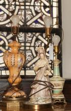 Group of three table lamps, one depicting woman in 19th century clothing, other two urn form composition with painted highlights