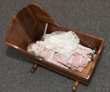 Two porcelain face dolls with soft bodies in wooden doll cradle