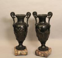 A Pair of Broze Urns on Marble bases.