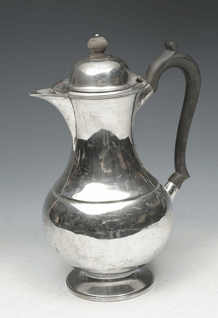 A SILVER WATER JUG of baluster form and scrolling