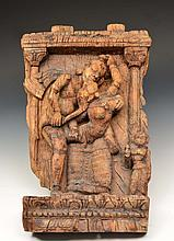 AN INDIAN CARVED WOODEN PANEL in the form of erotic figures within a niche, 42 x 22cm   100