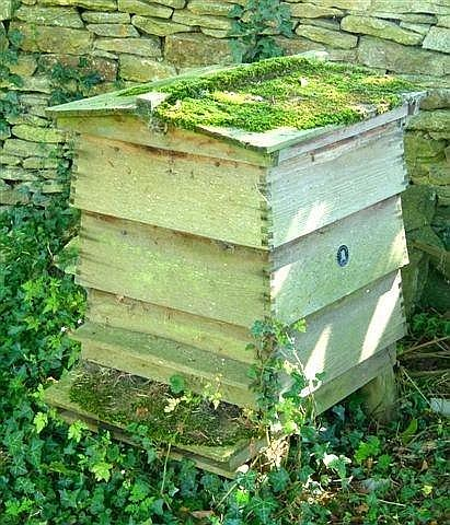 A WOODEN BEEHIVE by E H Taylor, Beehive Works, Welwyn, Herts, 25in x 22in, together with assorted beekeeping equipment. (see illustration)