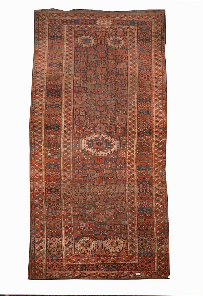 AN OLD BESHIR WINE GROUND HALL CARPET decorated a
