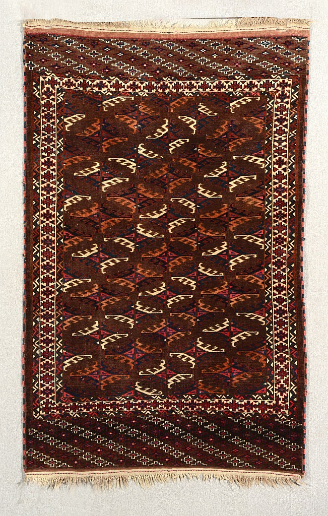 A YOMUT WINE GROUND RUG decorated six rows of