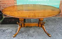 Oak oval dining table on twin tripod supports with cross st