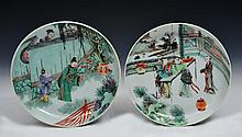 A PAIR OF CHINESE FAMILLE VERTE SHALLOW DISHES, lady looking over a wall at two figures in a garden,