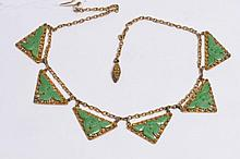 A CHINESE GILT NECKLACE with filigree decoration and carved jade setting, stamped China, silver
