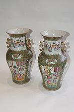 A PAIR OF CHINESE CANTON BALUSTER VASES with panels of figures amongst green and foliate surrounds,