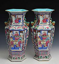 A PAIR OF CHINESE FAMILLE ROSE HEXAGONAL VASES decorated with four panels showing figures in court s