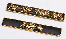TWO JAPANESE GOTA SCHOOL KOZUKA decorated in gilt, one showing a shi shi on a four legged pedestal,