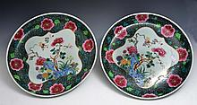 A CHINESE PAIR OF FAMILLE VERTE CHARGERS, each with chrysanthemums and peonies to the centre, late 1